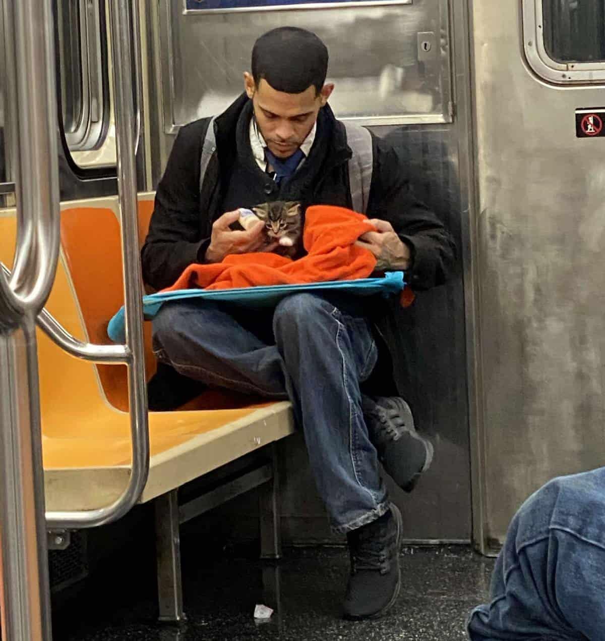 homem com gato bebe no colo a alimentar de biberão